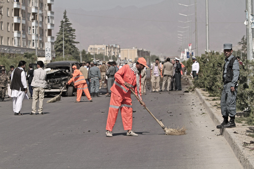 Afghanistan's municipality employees, in orange, clean the site of a suicide car bombing in Kabul, Afghanistan, Saturday, June 21, 2014. The bombing aimed at a senior government official killed one civilian and wounded three others on Saturday but did not harm its apparent target, Afghan security officials said. (AP Photo/Rahmat Gul)