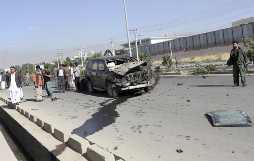 Afghanistan's security forces and officials inspect the site of a suicide car bombing in Kabul, Afghanistan, Saturday, June 21, 2014. The bombing aimed at a senior government official killed one civilian and wounded three others on Saturday but did not harm its apparent target, Afghan security officials said. (AP Photo/Rahmat Gul)