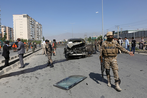 Afghanistan's security forces inspect the site of a suicide car bombing in Kabul, Afghanistan, Saturday, June 21, 2014. The bombing aimed at a senior government official killed one civilian and wounded three others on Saturday but did not harm its apparent target, Afghan security officials said. (AP Photo/Rahmat Gul)