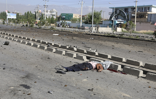 EDS NOTE: GRAPHIC CONTENT - The dead body of a civilian lies on the ground at the site of a suicide car bombing in Kabul, Afghanistan, Saturday, June 21, 2014. The bombing aimed at a senior government official killed the civilian and wounded three others on Saturday but did not harm its apparent target, Afghan security officials said. (AP Photo/Rahmat Gul)