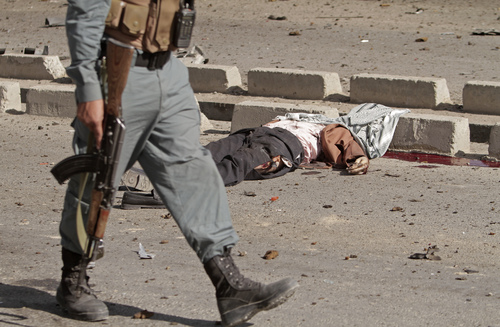 EDS NOTE: GRAPHIC CONTENT - An Afghan police officer walks past the body of a civilian lying on the ground at the site of a suicide car bombing in Kabul, Afghanistan, Saturday, June 21, 2014. The bombing aimed at a senior government official killed the civilian and wounded three others on Saturday but did not harm its apparent target, Afghan security officials said. (AP Photo/Rahmat Gul)