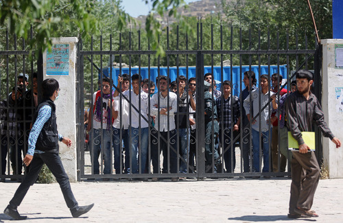 Students watch supporters of presidential candidate Abdullah Abdullah shout slogans during a protest in Kabul, Afghanistan, Saturday, June 21, 2014. Former Foreign Minister Abdullah, who is running against Ashraf Ghani Ahmadzai, a former finance minister, has accused electoral officials and others of trying to rig the June 14 vote against him. (AP Photo/Massoud Hossaini)