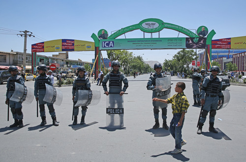 An Afghan boy walks past Afghanistan police forces standing guard during a protest by supporters of presidential candidate Abdullah Abdullah in Kabul, Afghanistan, Saturday, June 21, 2014. Former Foreign Minister Abdullah, who is running against Ashraf Ghani Ahmadzai, a former finance minister, has accused electoral officials and others of trying to rig the June 14 vote against him. (AP Photo/Massoud Hossaini)