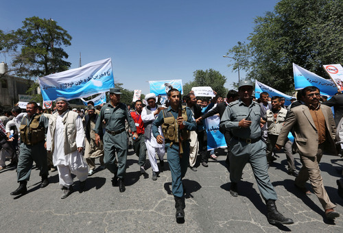 Afghan police officers secure the area as supporters of presidential candidate Abdullah Abdullah holds a protest in Kabul, Afghanistan, Saturday, June 21, 2014. Former Foreign Minister Abdullah, who is running against Ashraf Ghani Ahmadzai, a former finance minister, has accused electoral officials and others of trying to rig the June 14 vote against him. (AP Photo/Rahmat Gul)