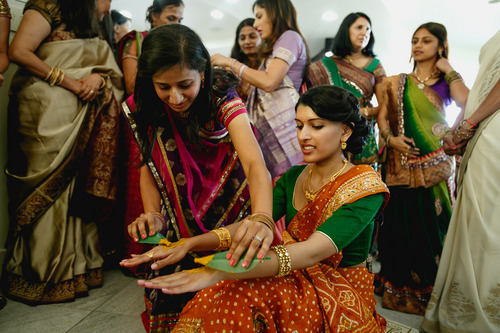 photo courtesy Nadia D Photography  Female relatives paint sacred turmeric onto the hands and legs of bride Avni Patel in a purification ritual during the first day of a traditional three-day Indian wedding ceremony in Holladay Thursday, July 19, 2014. The wedding concludes Saturday.