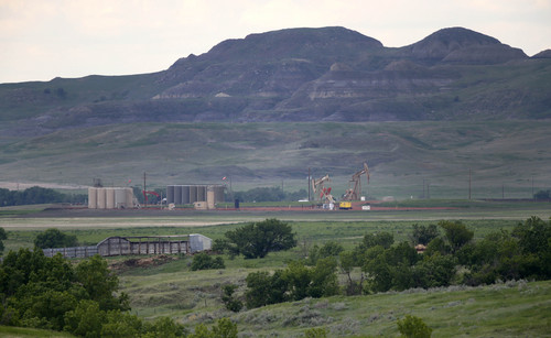 In this Wednesday, June 11, 2014 photo, oil production can be seen within the scenic views of the Theodore Roosevelt National Park, located in the Badlands of North Dakota. Some visitors have reported hearing the sounds of the oil industry deep inside the park. The Little Missouri River and the park's canyons can amplify noise from miles away, making the development seem even closer. Oil development is strictly forbidden within the park itself, but park officials worry that the flares and noise from drilling just beyond the protected area sullies the natural spaces that drew Roosevelt here as a bespectacled young man in his mid-20s. (AP Photo/Charles Rex Arbogast)
