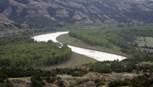 In this Wednesday, June 11, 2014, photo, the scenic Little Missouri River winds it's way inside the Theodore Roosevelt National Park located in the Badlands of North Dakota. The park of more than 70,000 acres sits atop the Bakken shale, an oil-rich rock formation that for decades frustrated drillers who could not coax anything profitable from the ground. But advances in hydraulic fracturing and directional drilling have unlocked huge amounts of petroleum here. North Dakota is now the second-biggest oil producer in the U.S. after Texas. Oil development is strictly forbidden within the park itself, but park officials worry that the flares and noise from drilling just beyond the protected area sullies the natural spaces that drew Roosevelt here as a bespectacled young man in his mid-20s. (AP Photo/Charles Rex Arbogast)