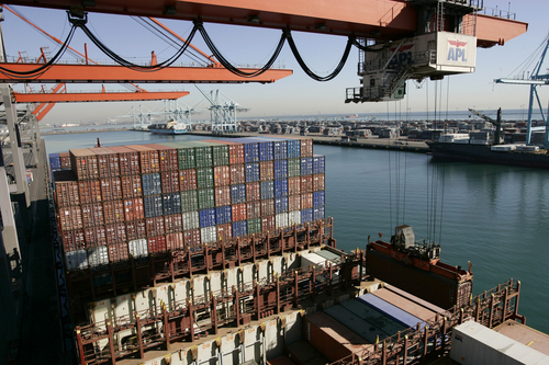 FILE - In this Dec. 4, 2006 file photo, shows are unloaded from the APL Singapore vessel at the port of Los Angeles. The West Coast ports that are America's gateway for hundreds of billions of dollars of trade with Asia and beyond are no stranger to labor unrest and even violence. Now, the contract that covers nearly 20,000 dockworkers is set to expire, and businesses that trade in everything from apples to iPhones are worried about disruptions _ as the summer cargo crush begins. (AP Photo/Damian Dovarganes,file)