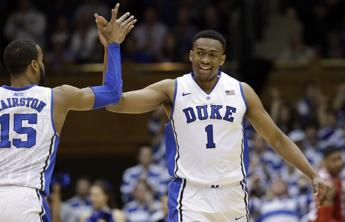 Duke's Josh Hairston (15) and Jabari Parker (1) high-fives following a play during the first half of an NCAA college basketball game against North Carolina State in Durham, N.C., Saturday, Jan. 18, 2014. Duke won 95-60. (AP Photo/Gerry Broome)
