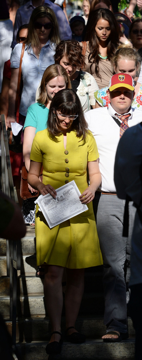Steve Griffin  |  The Salt Lake Tribune   Carrying her marriage certificate, Kate Kelly, founder of the The Ordain Women organization, walks with hundreds of supporters to the LDS Church Office Building during a vigil in Salt Lake City, Utah Sunday, June 22, 2014.  The event coincided with the church disciplinary court underway at Kate's former stake center in Virginia. Kate no longer lives in Virginia, and is living in Utah before she moves to Kenya with her husband..