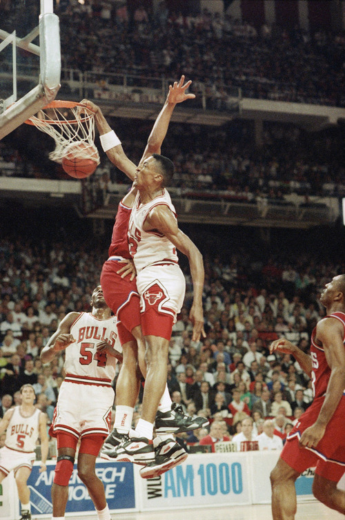 Chicago Bulls' Scottie Pippen slams home two points despite the efforts of Philadelphia 76ers' Charles Barkley during first half playoff action, Monday night, May 7, 1990 in Chicago. Watching the play is the Bulls' Horace Grant (54). (AP Photo/Charles Bennett)