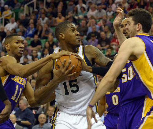 Rick Egan  |  The Salt Lake Tribune  Utah Jazz center Derrick Favors (15) trees to keep control of the ball, as he its triple teamed by Los Angeles Lakers forward Wesley Johnson (11), Los Angeles Lakers center Robert Sacre (50), and Los Angeles Lakers forward Ryan Kelly (4), in NBA action, The Utah Jazz vs. The Los Angeles Lakers, at EnergySolutions Arena, Monday, April 14, 2014