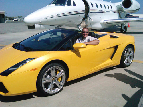 Utah Attorney General Mark Shurtleff poses behind the wheel of Jeremy Johnson's Lamborghini, in front of Johnson's jet, during a fundraiser in Southern California. Facebook Photo