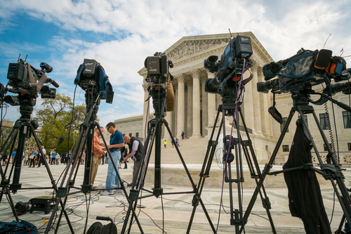 FILE - This April 22, 2014 file photo shows videojournalists seting up outside of the Supreme Court in Washington, where the court was hearing arguments between Aereo, Inc., an internet startup company that gives subscribers access to broadcast television on their laptops and other portable devices and the broadcasters.  The Supreme Court has ruled that a startup Internet company has to pay broadcasters when it takes television programs from the airwaves and allows subscribers to watch them on smartphones and other portable devices. The justices said Wednesday by a 6-3 vote that Aereo Inc. is violating the broadcasters' copyrights by taking the signals for free. The ruling preserves the ability of the television networks to collect huge fees from cable and satellite systems that transmit their programming.  (AP Photo/J. David Ake, File)