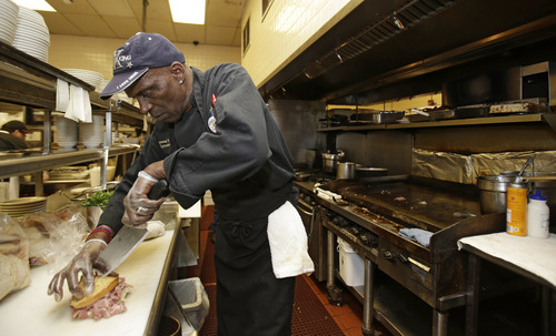 In this Friday, June 6, 2014 photo, executive chef Raymond Nicholson cuts a corned beef reuben sandwich at Corky & Lenny's Restaurant & Deli in Woodmere Village, Ohio. The Commerce Department releases first-quarter gross domestic product on Wednesday, June 25, 2014. (AP Photo/Tony Dejak)