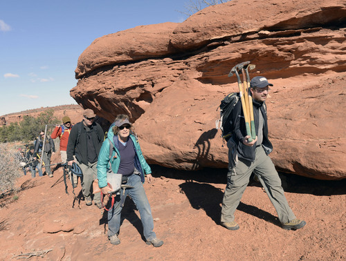 Al Hartmann  |  The Salt Lake Tribune  Volunteers with the Natural History Museum of Utah hike overland with equipment to a fossil site near Canyonlands National Park.