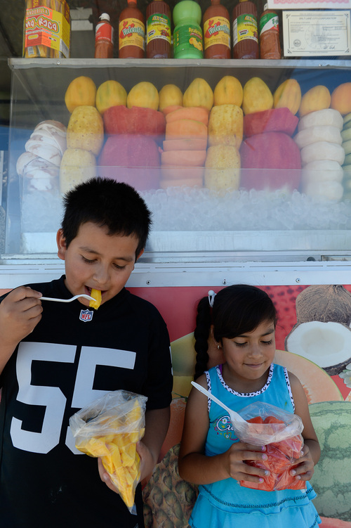 Francisco Kjolseth  |  The Salt Lake Tribune Bryan Miron, 9, left, and his sister Lizbeth, 6, enjoy a bag of fresh fruit at one of the newest and most unique carts known as Memos Fruit Cart on Redwood Road (In the parking lot of Lucero's Tires). Owner Nemorio Flores and his son Ryan serve fruit (coconut, papaya, watermelon, jicama, cantaloupe and cucumber) topped with chile powder or other seasonings. These carts are super popular in LA, but this is the first one in SLC.  The cart also sells Tostitos Locos (chips topped with cucumbers, jicama and pig skins and served in the chip bag) and the PiÒa Loca, a hollowed-out pineapple filled with pineapple and mangos.