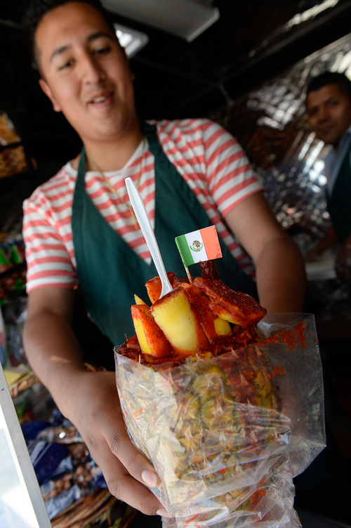 Francisco Kjolseth  |  The Salt Lake Tribune Ryan Flores serves up a hollowed-out piÒa filled with the cut pineapple and fresh mango covered in tajin and chamoy for a customer. One of the newest and most unique is Memos Fruit Cart on Redwood Road (in the parking lot of Lucero's Tires). Owner Nemorio Flores and his son Ryan serve fruit (coconut, papaya, watermelon, jicama, cantaloupe and cucumber) topped with chile powder or other seasonings. These carts are super popular in LA, but this is the first one in SLC. The cart also sells Tostitos Locos, chips topped with cucumbers, jicama and pig skins and served in the chip bag.