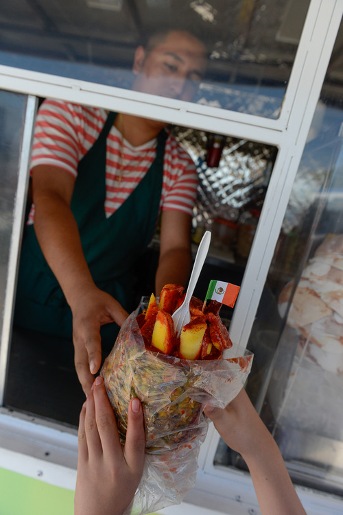 Francisco Kjolseth  |  The Salt Lake Tribune Ryan Flores serves up a hollowed-out piña filled with the cut pineapple and fresh mango covered in tajin and chamoy for a customer. One of the newest and most unique is Memos Fruit Cart on Redwood Road (In the parking lot of Lucero's Tires). Owner Nemorio Flores and his son Ryan serve fruit (coconut, papaya, watermelon, jicama, cantaloupe and cucumber) topped with chile powder or other seasonings. These carts are super popular in LA, but this is the first one in SLC. The cart also sells Tostitos Locos, chips topped with cucumbers, jicama and pig skins and served in the chip bag.