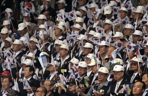 South Korean war veterans wave their national flags during a ceremony to mark the 64th anniversary of the outbreak of the Korean War in Seoul, South Korea, Wednesday, June 25, 2014. The three-year Korean War broke out on June 25, 1950, when Soviet tank-led North Koreans invaded South Korea. (AP Photo/Ahn Young-joon)