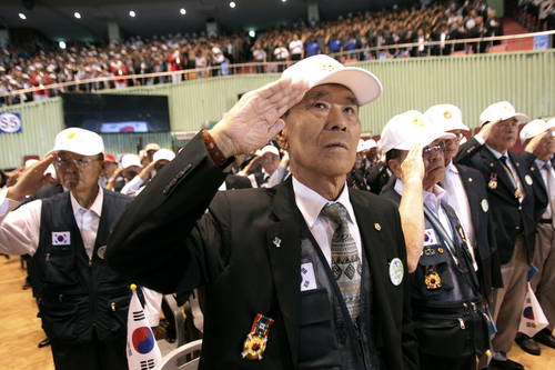 South Korean war veterans salute during a ceremony to mark the 64th anniversary of the outbreak of the Korean War in Seoul, South Korea, Wednesday, June 25, 2014. The three-year War broke out on June 25, 1950, when Soviet tank-led North Koreans invaded South Korea. (AP Photo/Ahn Young-joon)