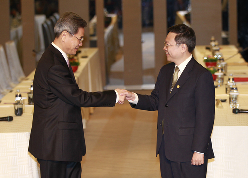 Zhang Zhijun, minister of Beijing's Taiwan Affairs Office, left, and his Taiwan counterpart Wang Yu-chi shake hands at the start of their meeting in Taoyuan, Taiwan, Wednesday, June 25, 2014. China has sent Zhang, its first ever ministerial-level official to Taiwan for four days of meetings to rebuild ties with the self-ruled island that Beijing claims as its own, after mass protests in Taipei set back relations earlier this year. (AP Photo/Wally Santana)