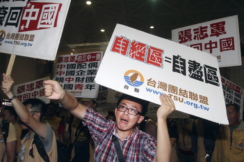"""A protester shouts slogans with a placard reading """"Free Economic Area = Suicide Area""""  as Zhang Zhijun, minister of Beijing's Taiwan Affairs Office, arrived at airport in Taoyuan county, Taiwan, Wednesday, June 25, 2014. China has sent Zhang, its first ever ministerial-level official to Taiwan for four days of meetings to rebuild ties with the self-ruled island that Beijing claims as its own, after mass protests in Taipei set back relations earlier this year. (AP Photo/Chiang Ying-ying)(AP Photo/Chiang Ying-ying)"""