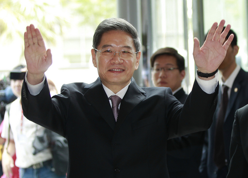 Zhang Zhijun, minister of Beijing's Taiwan Affairs Office, waves at the airport hotel upon arrival in Taoyuan, Taiwan, Wednesday, June 25, 2014. China has sent Zhang, its first ever ministerial-level official to Taiwan for four days of meetings to rebuild ties with the self-ruled island that Beijing claims as its own, after mass protests in Taipei set back relations earlier this year. (AP Photo/Wally Santana)