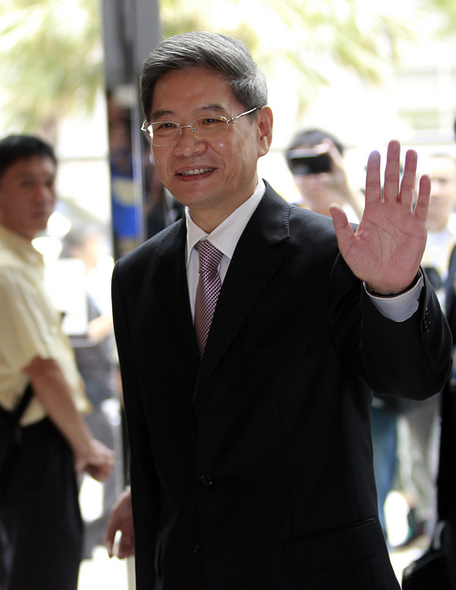 Zhang Zhijun, minister of Beijing's Taiwan Affairs Office, waves at the airport hotel after arriving in Taoyuan, Taiwan, Wednesday, June 25, 2014. China has sent Zhang, its first ever ministerial-level official to Taiwan for four days of meetings to rebuild ties with the self-ruled island that Beijing claims as its own, after mass protests in Taipei set back relations earlier this year. (AP Photo/Wally Santana)