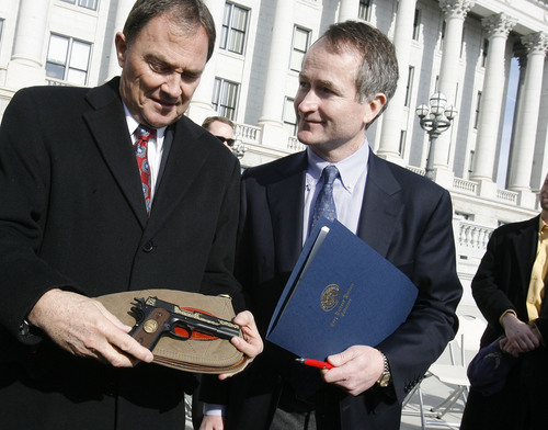 Scott Sommerdorf  l  The Salt Lake Tribune Utah Governor Gary Herbert (left), holds the commemorative .22 cal Browning handgun given to him by Christopher Browning, (right), the great grandson of John M. Browning, Monday, 1/24/2011. The Governor made a formal presentation of the resolution declaring Monday. 1/24/2011 as John M. Browning Day to Christopher Browning, the great grandson of John M. Browning, at the noon ceremony on the capitol steps.