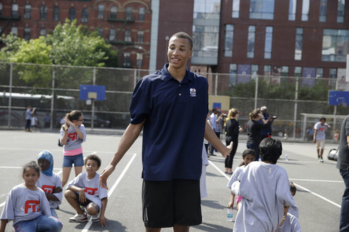 Australian basketball player Dante Exum congratulates kids during a basketball clinic in New York, Wednesday, June 25, 2014. Exum and other 2014 draft prospects are in town for the NBA draft in Brooklyn, New York on June 26, 2014. (AP Photo/Seth Wenig)