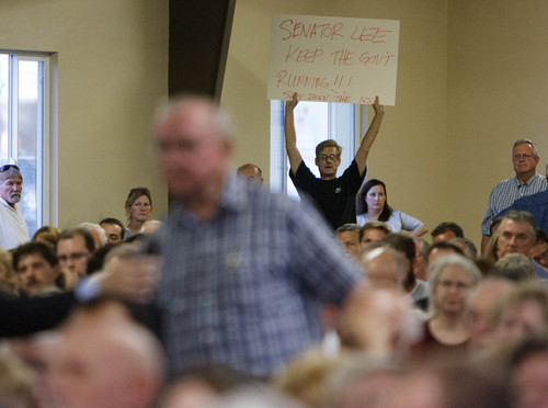 """Trent Nelson     The Salt Lake Tribune Doug Vowles holds up a sign, reading """"Senator Lee: Keep the Gov't Running!!! Shut Down the NSA,"""" as Senator Mike Lee meets with constituents at a townhall meeting in Spanish Fork, Wednesday August 21, 2013."""