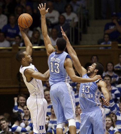 Duke's Rodney Hood, left, shoots as North Carolina's J.P. Tokoto (13) and James Michael McAdoo (43) defend during the first half of an NCAA college basketball game in Durham, N.C., Saturday, March 8, 2014. (AP Photo/Gerry Broome)