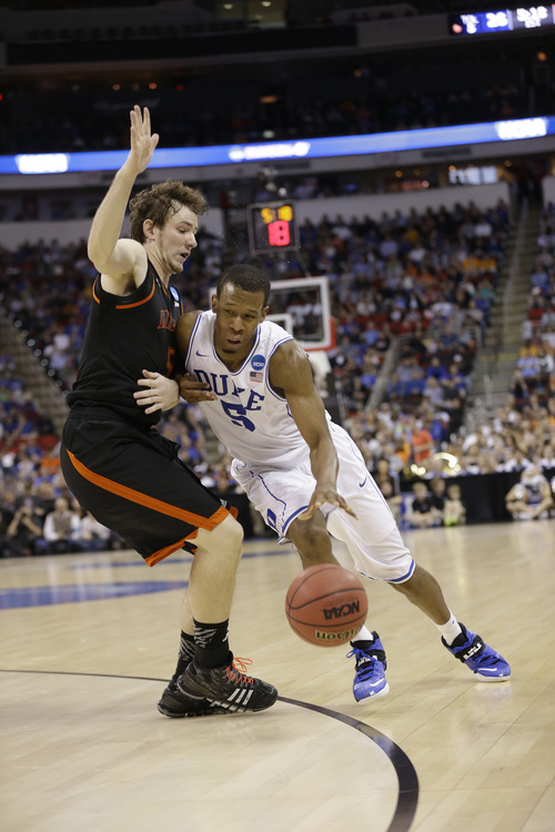 Duke forward Rodney Hood (5) moves against Mercer forward Bud Thomas (5) during the first half of an NCAA college basketball second-round game, Friday, March 21, 2014, in Raleigh, N.C. (AP Photo/Gerry Broome)