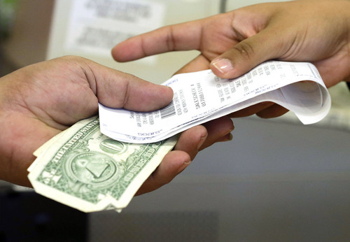 FILE - In this Friday, Nov. 23, 2012 file photo, a cashier hands a customer his change and receipt during a transaction at a Sears store, in Henderson, Nev. The University of Michigan issues its index of consumer sentiment for June, 2014 on Friday, June 27, 2014. (AP Photo/Julie Jacobson, File)
