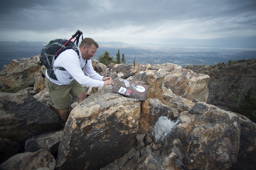 Rick Egan  |  The Salt Lake Tribune  Michael Hakkarinen, Cottonwood Heights, writes a note to place in the U.S. Forest Service register on June 26, 2014, near the spot where a flagpole was mounted in concrete on the Mount Olympus summit. An LDS Church spokeswoman acknowledged that missionaries from the Salt Lake City East mission erected the flagpole, which violates rules in the Mount Olympus Wilderness Area.