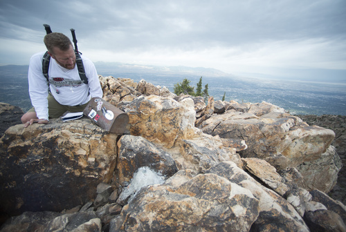 Rick Egan  |  The Salt Lake Tribune  Michael Hakkarinen, Cottonwood Heights, checks out the spot where a flagpole was mounted into cement, at the summit of Mount Olympus, June 26, 2014.