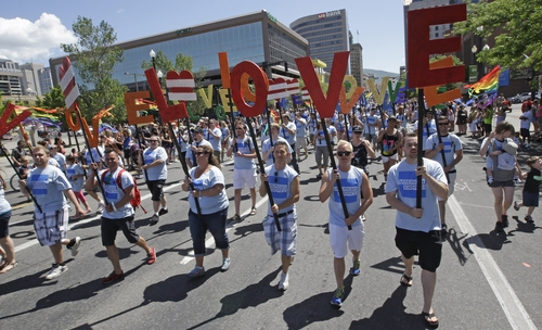 """In this June 8, 2014, photo, American Express workers carry giant, cutout letters that spelled, """"Love=Love,"""" the theme of the of the gay pride parade, in Salt Lake City. Corporations have increased visibility this summer at gay pride parades around the country as same-sex marriage bans fall in the courts and polls show greater public acceptance of gay marriage. (AP Photo/Rick Bowmer)"""