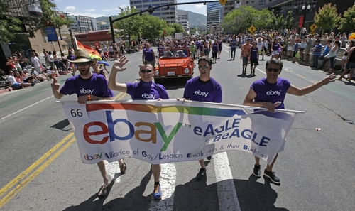In this June 8, 2014, photo, workers carry an eBay banner during the gay pride parade, in Salt Lake City. Corporations have increased visibility this summer at gay pride parades around the country as same-sex marriage bans fall in the courts and polls show greater public acceptance of gay marriage. (AP Photo/Rick Bowmer)
