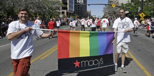 In this June 8, 2014, photo, workers carry a Macy's banner during the gay pride parade, in Salt Lake City. Corporations have increased visibility this summer at gay pride parades around the country as same-sex marriage bans fall in the courts and polls show greater public acceptance of gay marriage. (AP Photo/Rick Bowmer)