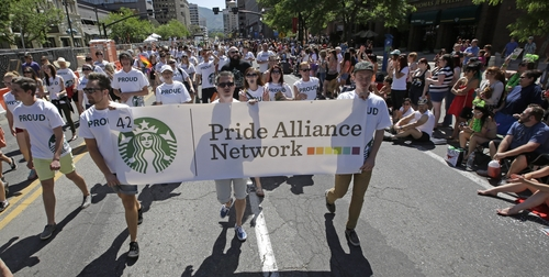 In this June 8, 2014, photo, workers carry a Starbucks banner during the gay pride parade, in Salt Lake City. In between muscular men in speedos gyrating to thumping dance music and drag queens decked out in formal gowns, Salt Lake City's recent gay pride parade also featured a few more conventional participants: Some of America's most well-known companies. From Starbucks to eBay to Macy's, the increasing visibility of corporations at the parade in Utah and others across the country each year comes as same-sex marriage bans fall in the courts and polls show greater public acceptance of gay marriage. (AP Photo/Rick Bowmer)