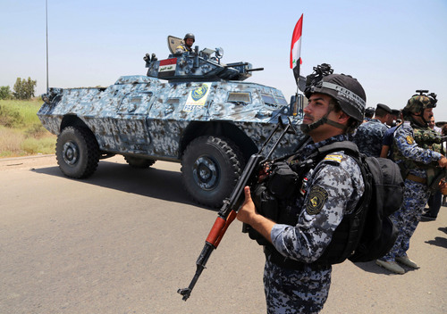 Iraqi federal policemen patrol in Baghdad's Abu Ghraib suburb, Iraq, Saturday, June 28, 2014. Iraqi troops backed by helicopter gunships launched an operation early Saturday aimed at dislodging Sunni militants from the northern city of Tikrit, one of two major urban centers they seized in recent weeks in a dramatic blitz across the country. (AP Photo/Karim Kadim)