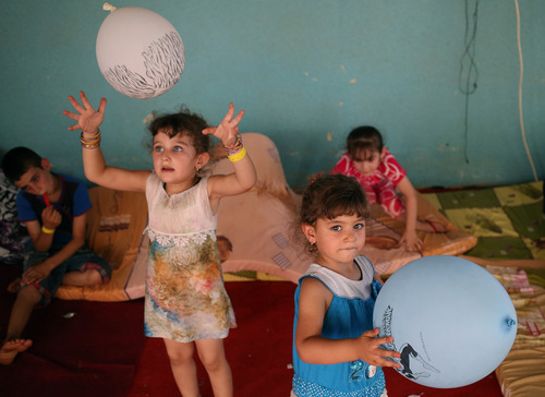 Displaced Iraqi Christian girls who fled with their parents from the Christian village of Hamdania near Mosul province in Iraq, play by their balloons at a temporary shelter for the displaced Christian families in Ainkawa, a suburb of Irbil, with a majority Christian population, Iraq, Saturday, June 28, 2014. Around 2,000 Christians had entered the Kurdish city of Irbil by Thursday morning, June 26. A Christian official there said the Kurdish region is the only part of Iraq where Christians are protected from violence. (AP Photo/Hussein Malla)