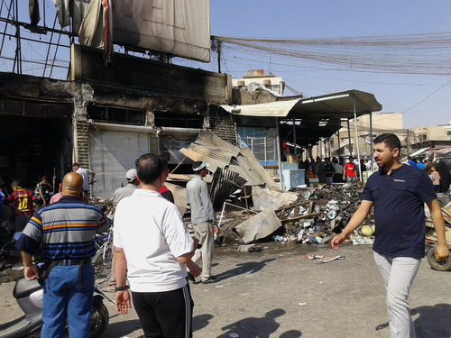 People inspect buildings damaged by an Iraqi government airstrike in the northern city of Mosul, Iraq, Saturday, June 28, 2014. The Iraq military carried out three airstrikes on the insurgent-held city of Mosul early Saturday. (AP Photo)