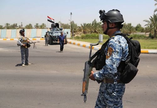 Iraqi federal policemen stand guard at a checkpoint outside of Baghdad International Airport, Iraq, Saturday, June 28, 2014. Iraqi troops backed by helicopter gunships launched an operation early Saturday aimed at dislodging Sunni militants from the northern city of Tikrit, one of two major urban centers they seized in recent weeks in a dramatic blitz across the country. (AP Photo/Karim Kadim)