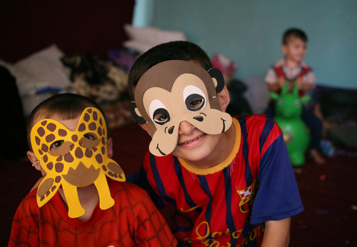 Displaced Iraqi Christian boys who fled with their parents from the Christian village of Hamdania near Mosul province in Iraq, wear masks at a temporary shelter for the displaced Christian families in Ainkawa, a suburb of Irbil, with a majority Christian population, Iraq, Saturday, June 28, 2014. Around 2,000 Christians had entered the Kurdish city of Irbil by Thursday morning, June 26. A Christian official there said the Kurdish region is the only part of Iraq where Christians are protected from violence. (AP Photo/Hussein Malla)