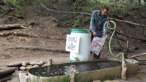 """(David Self Newlin   The Salt Lake Tribune)  Lionel Trepanier fills a water bag from a spring at the PR Springs campsite in eastern Utah. Utah Tar Sands Resistance is camping at PR Springs in what they call a permanent """"protest vigil"""" in an effort to stop development of tar sands in the area."""