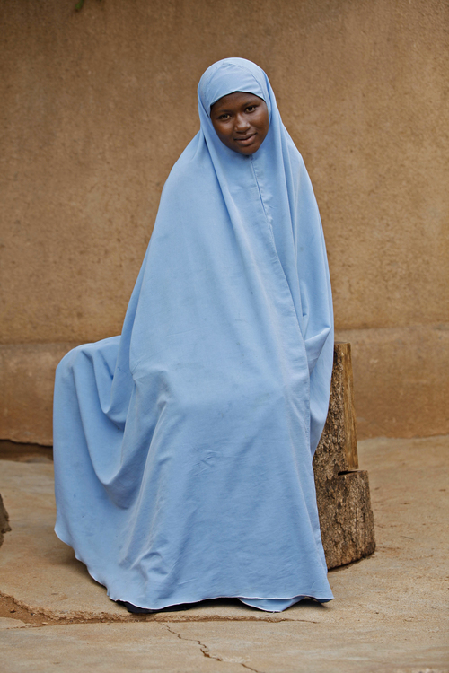 In this Sunday, June 1, 2014 photo, Maimuna Abdullahi sits outside her school in Kaduna, Nigeria. Maimuna wore the scars of an abused woman anywhere: A swollen face, a starved body, and, barely a year after her wedding, a divorce. But for Maimuna, it all happened by the time she was 13. Maimuna is one of thousands of divorced girls in Nigeria who were married as children and then got thrown out by their husbands or simply fled. (AP Photo/Sunday Alamba)