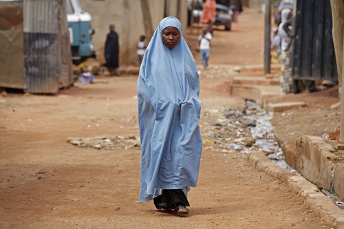 In this Sunday, June 1, 2014 photo, Maimuna Abdullahi walks to her home on a dirt road in Kaduna, Nigeria. Maimuna wore the scars of an abused woman anywhere: A swollen face, a starved body, and, barely a year after her wedding, a divorce. But for Maimuna, it all happened by the time she was 13. Maimuna is one of thousands of divorced girls in Nigeria who were married as children and then got thrown out by their husbands or simply fled. (AP Photo/Sunday Alamba)