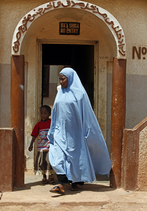 In this Saturday, May 31, 2014 photo, Maimuna Abdullahi, center, walks out of her home to school in Kaduna, Nigeria. Maimuna is one of thousands of divorced girls in Nigeria who were married as children and then got thrown out by their husbands or simply fled. (AP Photo/Sunday Alamba)